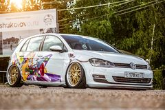 Moscow, Russia: July 06, 2019: Tuned by low suspension and custom wide golden colored wheels. White volkswagen golf 7 with