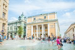 Birzhevaya square. The Chamber of Commerce and Industry of the Russian Federation. People splash in the fountain in hot weather royalty free stock photos