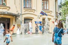 Birzhevaya square. People splash in the fountain in hot weather royalty free stock photo