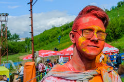 Moscow, Russia - June 3, 2017: Closeup portrait of teenager boy wearing glasses with face in paint after Holi-expression royalty free stock photo