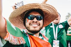 MOSCOW, RUSSIA - JUNE 2018: A happy Mexican fan with a flag and sombrero during the FIFA World Cup. MOSCOW, RUSSIA - JUNE 2018 A happy Mexican fan with a flag stock photography