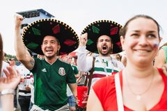 MOSCOW, RUSSIA - JUNE 2018: Happy Mexican fans in sombreros rejoice goal in the match Mexico - South Korea. MOSCOW, RUSSIA - JUNE 2018 Happy Mexican fans in stock images