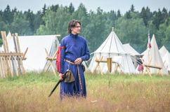 MOSCOW,RUSSIA-June 06,2016: Man in ancient warrior costume stands on green field of grass Stock Photo