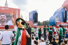 MOSCOW, RUSSIA - JUNE 2018: Mexican fan in uniform and sombrero watching the match Mexico - South Korea on fan fest. MOSCOW, RUSSIA - JUNE 2018 Mexican fan in stock images