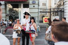 MOSCOW, RUSSIA - JUNE 2018: Polish football fan is photographed with Russian girls wearing hats in the center of Moscow royalty free stock photo