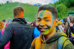 Moscow, Russia - June 3, 2017: Portrait of asian teenager boy with face stained with bright colors after festival Holi stock photos