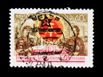 Man an woman workers, 10th anniversary of GDR, circa 1959. MOSCOW, RUSSIA - JUNE 26, 2017: Rsre stamp printed in USSR Russia shows man an woman workers, 10th stock image