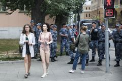 Russian policemen stand in a row, blocking the way to the metro. Two young girls on the background of the row of police. Moscow, RUSSIA - June 12, 2019: Russian royalty free stock photography