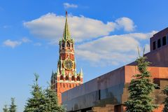 Moscow, Russia - June 28, 2018: Spasskaya tower of Moscow Kremlin on a background of Lenin`s Mausoleum against blue sky with white stock images
