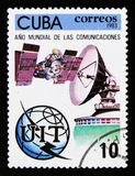 Cuba postage stamp shows sputnik, satellite antenna, globe and emblem, Year of comunication, circa 1983 Royalty Free Stock Photo