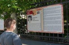 Moscow, Russia - June 02.2016. Teen boy reading a fragment of children's book of war on Myasnitskaya Street Stock Photo
