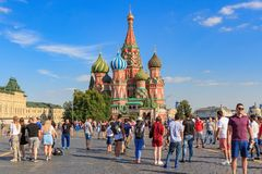 Moscow, Russia - June 28, 2018: Tourists walk on Red square on a background of St. Basil`s Cathedral in sunny summer evening Stock Photo