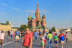 Moscow, Russia - June 28, 2018: Tourists walking on Red square on a background of St. Basil`s Cathedral in sunny summer evening Royalty Free Stock Photo