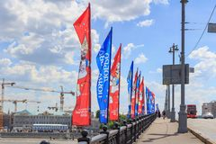 Moscow, Russia - June 03, 2018: Waving flags with symbols of FIFA World Cup Russia 2018 on Bol`shoy Kamennyy bridge on a blue sky. Background stock images