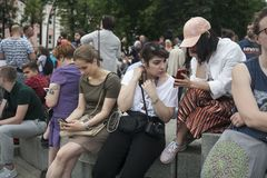 Young people with phones are sitting near the fountain. Moscow, RUSSIA - June 12, 2019: Young people with phones are sitting near the fountain royalty free stock images