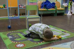 Little boy playing cars on the carpet. Entertainment of childhood. royalty free stock image
