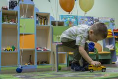Little boy playing cars on the carpet. Entertainment of childhood. stock photography