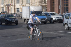 Moscow, Russia- 21.09.2015. Man on bike rides in traffic on Theatre Street Stock Image