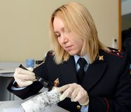Forensic expert police pulls fingerprints found on the can of the crime scene. MOSCOW, RUSSIA - MARCH 25, 2016: Forensic expert police pulls fingerprints found royalty free stock images
