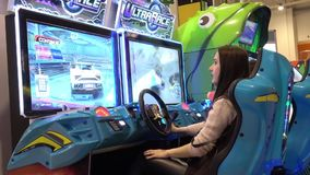Girl playing auto simulator video arcade game. Moscow, Russia - March, 2017: Girl playing auto simulator video arcade game stock footage