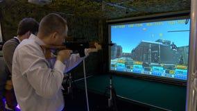 Man playing video arcade shooting rifle range game. Moscow, Russia - March, 2017: man playing video arcade shooting rifle range game stock video