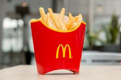 Moscow, Russia, March 15 2018: McDonald`s potato french fries in the red box on wooden background Royalty Free Stock Image