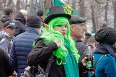 Participant in a green wig, hat and elf ears at the St. Patrick`s Day Parade in the park Sokolniki in Moscow stock image