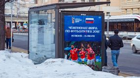 MOSCOW, RUSSIA - MARCH 28, 2018: Public transport stop with advertising billboard of the FIFA 2018 World Cup mundial. Snow on the street. People walk along the Royalty Free Stock Image