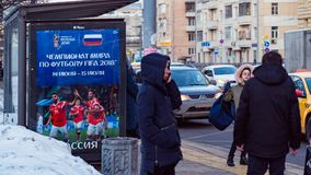 MOSCOW, RUSSIA - MARCH 28, 2018: Public transport stop with advertising billboard of the FIFA 2018 World Cup mundial. Snow on the street. People walk along the Stock Photography