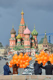 Moscow, Russia, March, 20, 2016, Russian scene: people with orange balloons in front of St. Basil`s Cathedral in Moscow. AncieMoscow, Russia, March, 20, 2016 Royalty Free Stock Photos