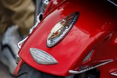 Moscow, Russia - May 04, 2019: Chrome and gold plated finish figurine of eagle head on a glossy red front fender of Honda tourist. Motorcycle closeup. Moto stock photography