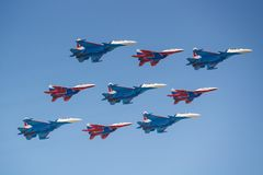 Moscow, Russia - May 07, 2019: Fighters Su-30SM and MiG-29 of Russian Knights and Swifts aerobatic teams in famous Kubinsky. Diamond over Red Square. Aviation stock photography
