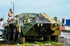 Moscow, Russia - May 25, 2019: Girl sit on a combat armored vehicle that stands on the field.  stock photo