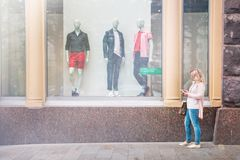 Moscow, Russia, May 22. 2018: the girl standing at the shop window of the famous brand.  Royalty Free Stock Photography
