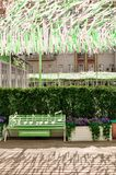Moscow, Russia - May, 05, 19. Music bench, beautiful flowers and pink,green, white ribbons fluttering in the wind on