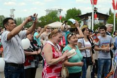 People during the celebration of Victory Day are watching a concert at the Exhibition of Economic Achievements. MOSCOW, RUSSIA - MAY 9, 2016:People during the Stock Image