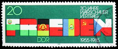 PEACE word formed from Flags, 30 Years The Warsaw Pact serie, circa 1985. MOSCOW, RUSSIA - MAY 25, 2019: Postage stamp printed in Germany, DDR, shows PEACE word royalty free stock image