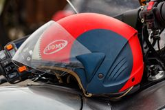 Moscow, Russia - May 04, 2019: Red and black motorcycle helmet Suomy with opened visor lies on a silvery fuel tank of motorcycle royalty free stock images