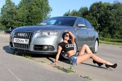 Moscow. Russia - May 20, 2019: Silver Audi A6 S line is parked on outdoor. Near sits the girl is the owner of the car in black t. Shirt with audi logo royalty free stock photos