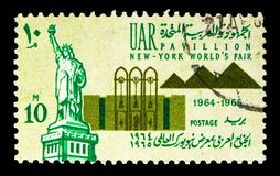 Statue of Liberty and World's Fair Pavilion - Pyramids, New Yo. MOSCOW, RUSSIA - MAY 13, 2018: A stamp printed in Egypt shows Statue of Liberty and World royalty free stock photo