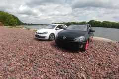 Moscow, Russia - May 03, 2019: Two toy cars in river park. 2 Volkswagen golf mk6 stand on a pebble beach. White and black GTI