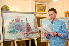 MOSCOW, RUSSIA, MAY 19, 2014: Unidentified teenager boy graduati. Ng the art school with his diploma painting works, May 19, 2014 Royalty Free Stock Image