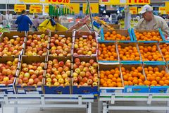 View of a rows of cartons boxes with apples and oranges in supermarket editorial. Moscow, Russia, may 2018: a view of a rows of cartons boxes with apples and Royalty Free Stock Photo
