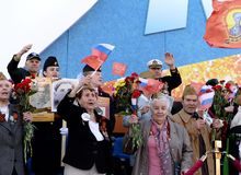 War veterans welcome the participants of the action `Immortal regiment` on the red square of Moscow. Stock Photo