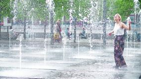 MOSCOW, RUSSIA - MAY, 24, 2017. Young woman having having fun in the park fountain. Hot summer in the city. MOSCOW, RUSSIA - MAY, 24, 2017. Young woman having stock images