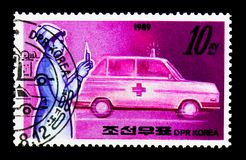 Nurse and ambulance, Public services serie, circa 1989. MOSCOW, RUSSIA - NOVEMBER 24, 2017: A stamp printed in Democratic People's republic of Korea shows Nurse Royalty Free Stock Photos
