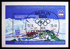 Mountains and cityscape, Winter Olympics 1976, Innsbruck serie, circa 1975. MOSCOW, RUSSIA - NOVEMBER 10, 2018: A stamp printed in Germany, Democratic Republic royalty free stock photo