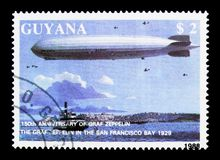 Graf Zeppelin over San Francisco, 150th Anniversary of the birth. MOSCOW, RUSSIA - NOVEMBER 25, 2017: A stamp printed in Guyana shows Graf Zeppelin over San stock photos