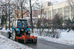 MOSCOW, RUSSIA - NOVEMBER 27, 2016:   Tractor cleaning up the  street after the night snowfall Stock Image