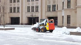 Snow cleaning tractor. MOSCOW, RUSSIA - NOVEMBER 25, 2017: Tractor cleaning up the street after the night snowfall stock video